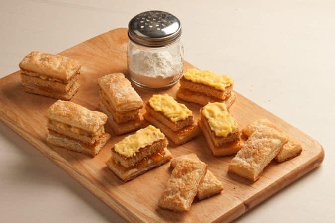 Spalma su 8 rettangoli di sfoglia un velo di marmellata, disponici sopra i rettangoli di pan di Spagna e spennellali con il rum;
