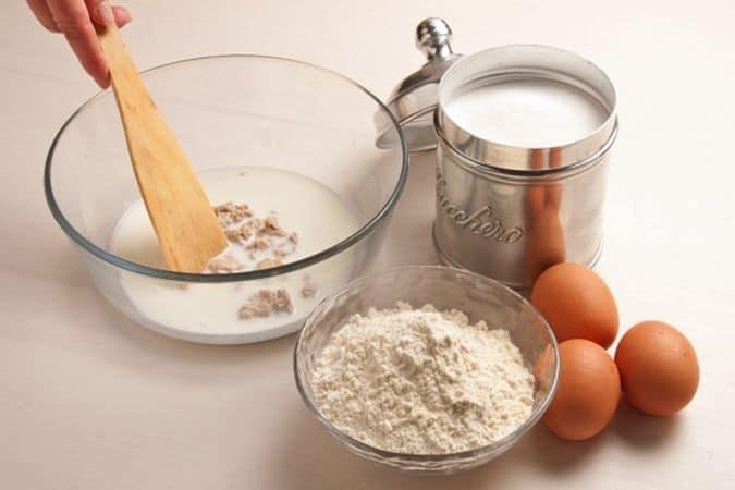 Prepara la pasta: mescola il lievito con il latte tiepido e un cucchiaio zucchero e lascia riposare per 15-20 minuti. Aggiungi la farina, la margarina, lo zucchero, la scorza di arancia e le uova. Impasta con cura fino a ottenere un composto elastico, lascialo lievitare, coperto, per 15-20 minuti. Dividi la pasta in 12-15 palline e disponile sulla placca del forno, rivestita di carta forno;
