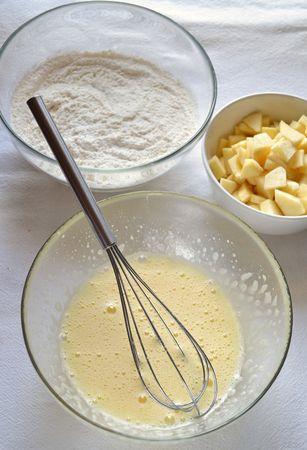 Accendete il forno a 180 gradi. Foderate la placca da forno con carta antiaderente. Mescolate farina e lievito, setacciate e mettete da parte. Pelate le mele e tagliatele a pezzetti piuttosto piccoli. Fate sciogliere la Vallé a bagnomaria (o nel microonde a potenza bassa) e mettete  da parte a raffreddare