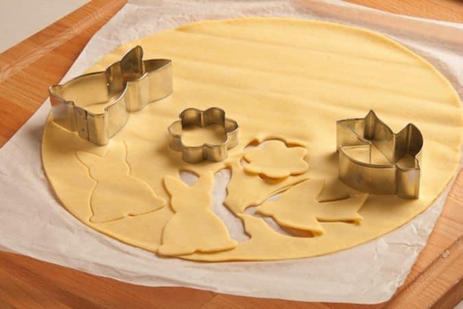 Srotola la pasta frolla e ritaglia i biscottini utilizzando dei taglia biscotti con sagome a tema pasquale