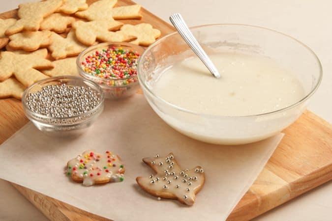 Distribuisci un velo di glassa su ciascun biscotto e aggiungi i confettini colorati e argentati per completare la decorazione. falli asciugare bene prima di servirli.