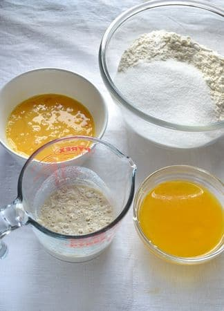 Partite con un giorno di anticipo: Fate sciogliere la Vallé a bagnomaria e mettete da parte. Fate intiepidire il latte (non troppo caldo) e unite il lievito, 1 cucchiaio di zucchero e 3 cucchiai di farina; mescolate, coprite e lasciate riposare in un luogo riparato per 15 minuti. Nel frattempo, mescolate farina e zucchero in una ciotola capiente e (sempre a parte) sbattete leggermente le uova e i tuorli. Versate il composto di lievito e latte (che nel frattempo si sarà attivato, facendo delle bolle) nella ciotola della farina e mescolate. Unite la margarina sciolta, le uova e mescolate ancora.
