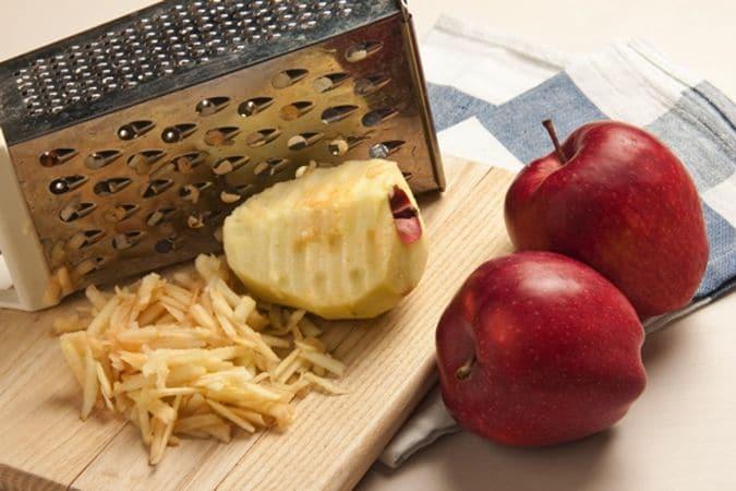 Metti i fiocchi d'avena nell'acqua bollente e lasciali riposare per 5 minuti, affinché si gonfino e si ammorbidiscano. Trascorso questo tempo aggiungi la farina setacciata con il lievito in polvere, il sale, lo zucchero e il latte e mescola bene. Fai fondere su fuoco bassissimo 60 g di margarina, senza che frigga, poi uniscila al composto. Sbuccia 2 mele, elimina i torsoli e grattugiale con la grattugia a buchi grandi;