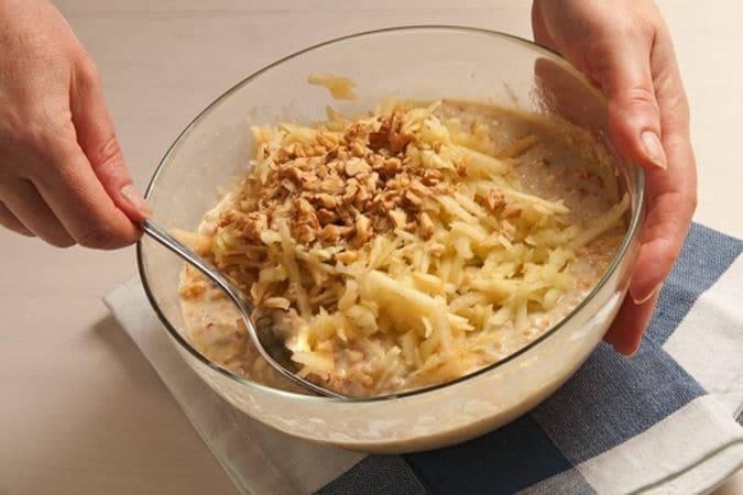 trita grossolanamente le noci. Unisci le mele e le noci al composto preparato e mescola con cura in modo da distribuirle uniformemente. Fai sciogliere in una padella antiaderente una noce della margarina rimasta e, quando sarà sciolta,
