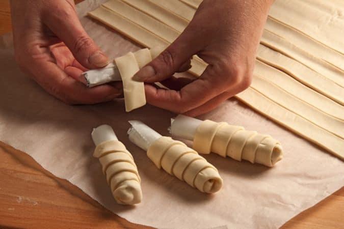 Srotola la pasta sfoglia e tagliala in modo da formare delle strisce di pasta dello spessore di 1,5 cm circa poi arrotola ciascuna striscia intorno a uno dei supporti preparati, in modo da dare forma a dei cornetti di sfoglia.