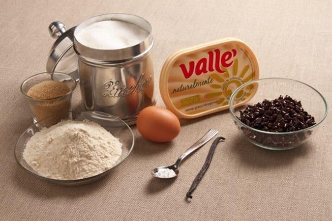 Sbatti, con lo sbattitore elettrico, la margarina con lo zucchero di canna e lo zucchero semolato, aggiungi l'uovo e mescola fino a ottenere un composto soffice e uniforme.<br />  Incorpora la farina setacciata insieme con il lievito e al sale poi aggiungi anche i semini di vaniglia e le gocce di cioccolato.