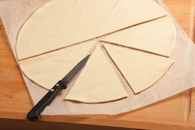 Stendi il rotolo di pasta sfoglia sul piano di lavoro e, utilizzando un coltellino ben affilato, taglialo in 8 spicchi.