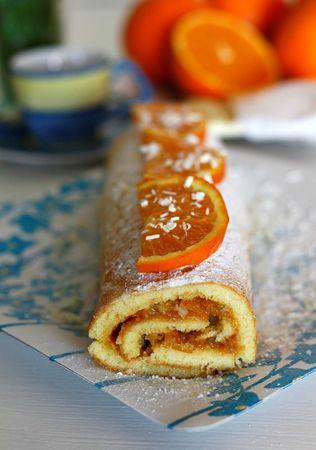 Spolverizzare di zucchero a velo e decorare con fettine di arancia e scaglie di cioccolato bianco