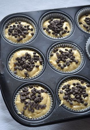 Dividete l'impasto nei pirottini e lasciate cadere una presa di gocce di cioccolato su ogni muffin
