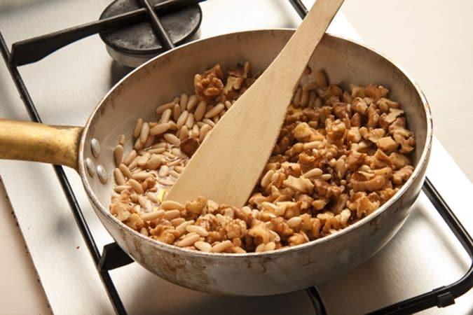 Bucherella, con i rebbi di una forchetta, il fondo poi riempi con i fagioli secchi e cuoci, nel forno preriscaldato a 180° per 15/20 minuti. Nel frattempo fai sciogliere il miele in un padellino e aggiungi le noci tritate grossolanamente e i pinoli;