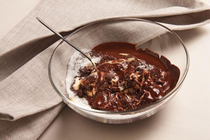 Spezzetta il cioccolato e fallo fondere a bagno maria poi versalo in una ciotola e mescolalo con lo zucchero, la margarina e i tuorli;