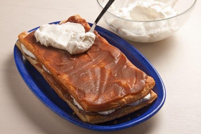 Monta la panna, ben fredda, con lo zucchero a velo. Disponi un rettangolo di pasta sul piatto di portata e spalmalo con uno strato di crema di marroni; su questa fai uno strato di panna, poi ricopri con altra pasta sfoglia e procedi nello stesso modo.