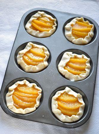Sistemate le fettine di pesca sulla crema, distribuite lo zucchero rimasto sulle pesche e ripiegate i bordi verso l'interno del dolce. Infornate per 25-30 minuti
