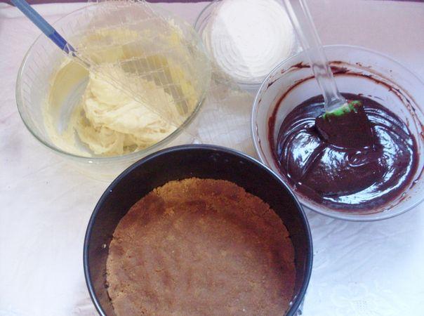 Tritare i biscotti con le mandorle, aggiungere la valle' fusa e rivestire uno stampo (diametro 20 cm) con carta forno. Pressare bene il tutto e riporre la teglia in frigo. Nel frattempo preparare le due creme al cioccolato: tritare il differente tipo di cioccolato e aggiungerlo rispettivamente alla panna liquida indicata. Sciogliere ciascuna al microonde ed aggiungere la colla di pesce ammorbidita. Mescolare e mettere a raffreddare le due ciotole. Una volta fredda montare con un frullino la crema al cioccolato bianco ed aggiungere a questa la ricotta.