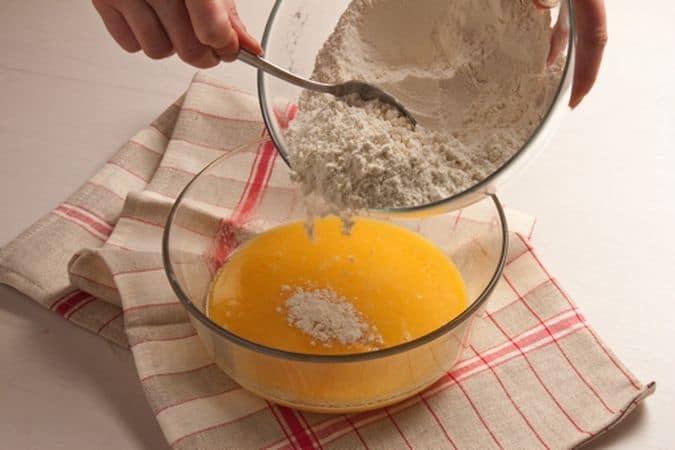Mescola la farina con lo zucchero, il lievito e un pizzico di sale. Fai sciogliere la margarina in un padellino su fuoco bassissimo. Versala in una ciotola e mescolala con le uova e il latte. Versa la miscela di farina e zucchero nel composto liquido e mescola con cura.