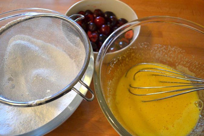 Mescolate la farina e il lievito e setacciate; lavate, denocciolate le ciliegie e tagliatele a metà; sbattete le uova con lo zucchero semolato e la vaniglia