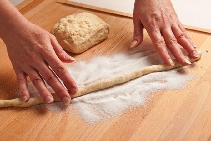 Riprendi l'impasto, dividilo a pezzettini e forma di bastoncini lunghi e sottili; cospargi il piano di lavoro con un po' di zucchero semolato e passaci sopra i bastoncini facendo in modo che risultino ben coperti.