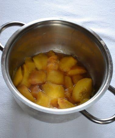 Mentre la torta si raffredda, cuocete le pesche: sbucciate i frutti, privateli del nocciolo e tagliateli a pezzetti. Mettete le pesche in una casseruola dal fondo pesante, unite il succo di limone, circa 50 ml di acqua e mettete sul fuoco medio. Appena la frutta prende bollore, coprite e abbassate il fuoco. Fate cuocere per 5-8 minuti finché la frutta inizia a sfaldarsi, poi spegnete, togliete la frutta dalla pentola con una schiumarola,  mettetela in una ciotola o un piatto e schiacciatela con una forchetta finché è calda in modo da ridurla in purè. Conservate lo sciroppo rimasto nella pentola, servirà dopo; conservate il tutto in frigo fino al momento di assemblare la charlotte