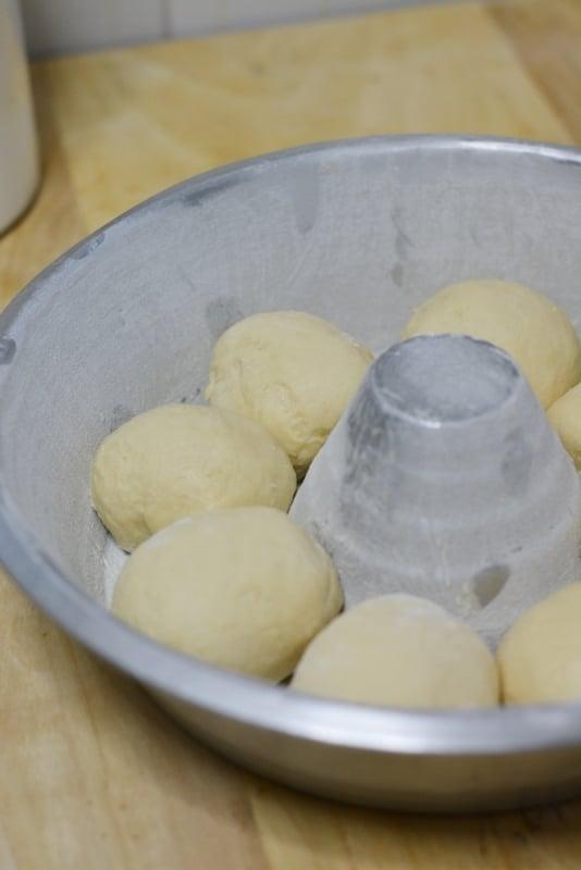 Tirare fuori dal frigo l'impasto e dividerlo in 8 palline e sistemarlo in uno stampo a ciambella imburrata ed infarinato.
