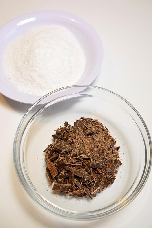 Sciogliete il cioccolato aggiungendo un goccio di latte quindi immergete i pezzi di torta e poi rotolateli nel cocco.
