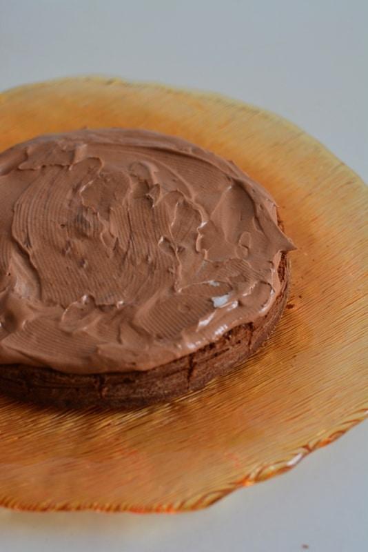 Preparare la farcia aggiungendo alla panna montata, 2 cucchiai di crema al cioccolato spalmabile. Farcire la torta solo una volta che si è completamente raffreddata