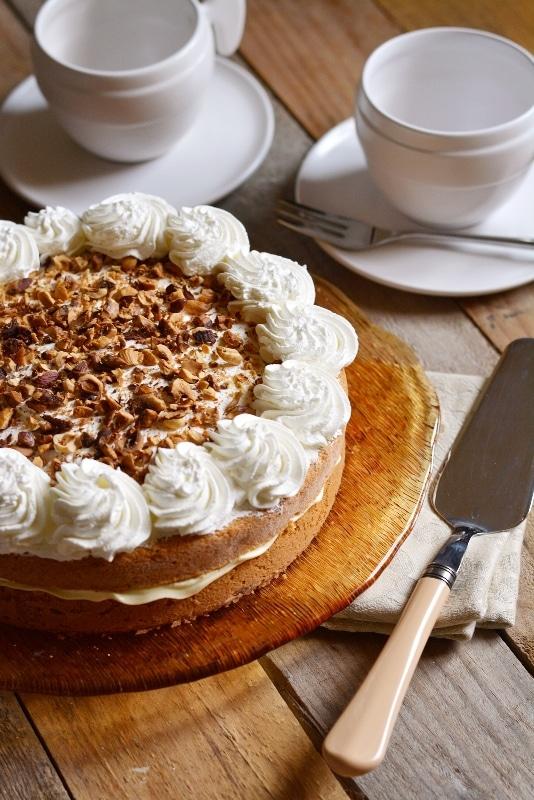 decorate la torta con dei ciuffi di panna e della granella di nocciole