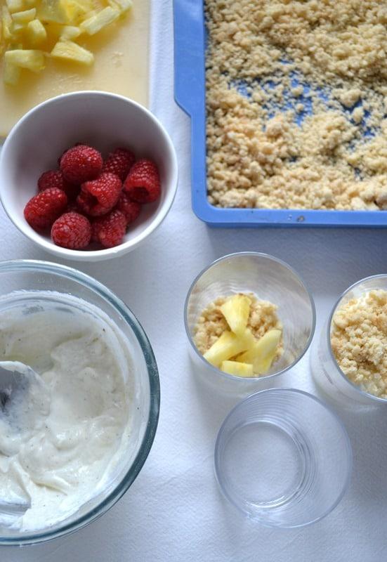Quando il crumble è freddo, sgranatelo con le mani e mettete da parte. Lavate e asciugate i lamponi. Tagliate l'ananas a pezzetti. Versate lo yogurt in una ciotola, unite lo zucchero, i semi contenuti nel baccello di vaniglia e mescolate. Formate i bicchierini alternando crumble, frutta e yogurt.