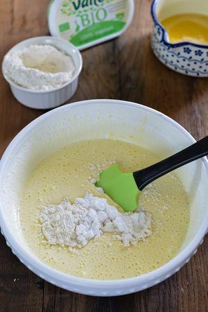 Aggiungete poco alla volta la farina, la fecola e il lievito setacciati insieme, mescolando con una spatola con movimento dal basso verso l'alto ruotano la ciotola.