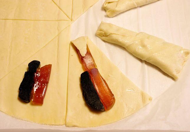 Fare lo stesso con l'altra metà Tagliarla in 8 spicchi. <br /> Dividere per il lungo i fruttini e disporli nei triangoli alternando i gusti.