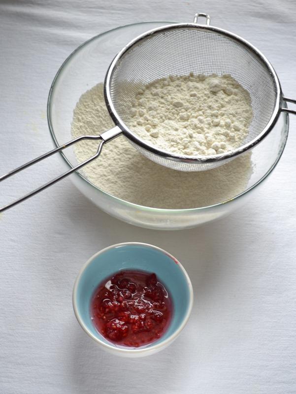 Accendete il forno a 180 gradi. Ungete e infarinate uno stampo da 6 ciambelline (8 cm diametro l'una). Mettete i lamponi che userete per la glassa in una ciotolina, unite il succo di limone e schiacciateli. Coprite con pellicola e mettete in frigo a macerare. Versate farina e lievito in una ciotola, setacciate e mettete da parte.