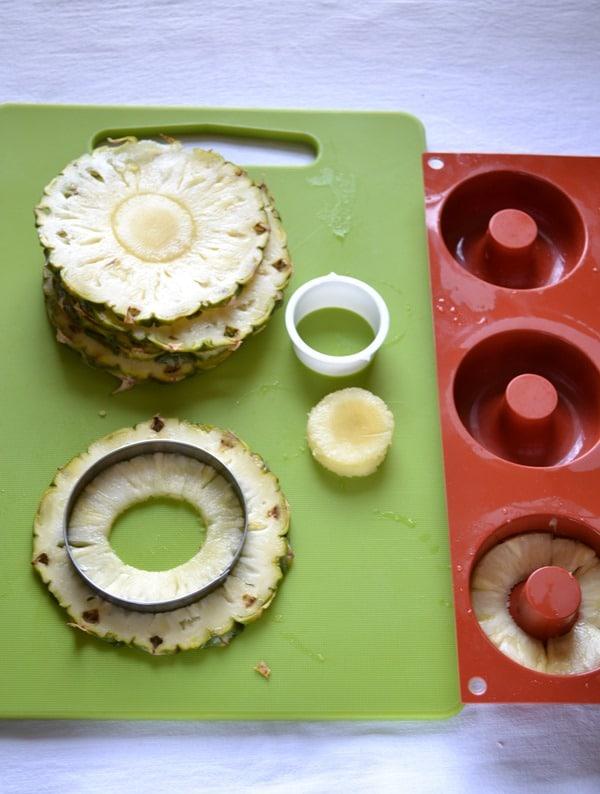 Accendete il forno a 180 gradi. Ungete uno stampo per ciambelline (8 cm diametro l'una). Tagliate l'ananas i 6 parti spesse circa 1 cm, poi eliminate la parte dura al centro e ritagliate i bordi in modo che le fette siano della grandezza degli stampini. Mettete da parte.