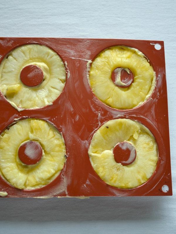 Dividete l'impasto negli stampi (riempiteli per ¾) , coprite ogni ciambella con una fetta d'ananas, schiacciate delicatamente e infornate per 25 minuti circa (fate la prova stecchino).