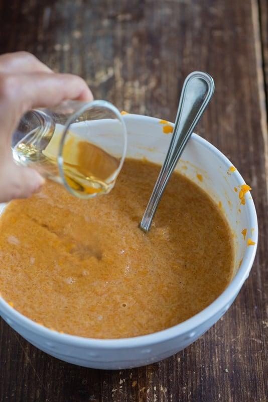 Trasferite la zucca in una terrina, schiacciatela bene con una forchetta, unite lo zucchero di canna, l'uovo, la panna, le spezie e il vino liquoroso o il cognac.