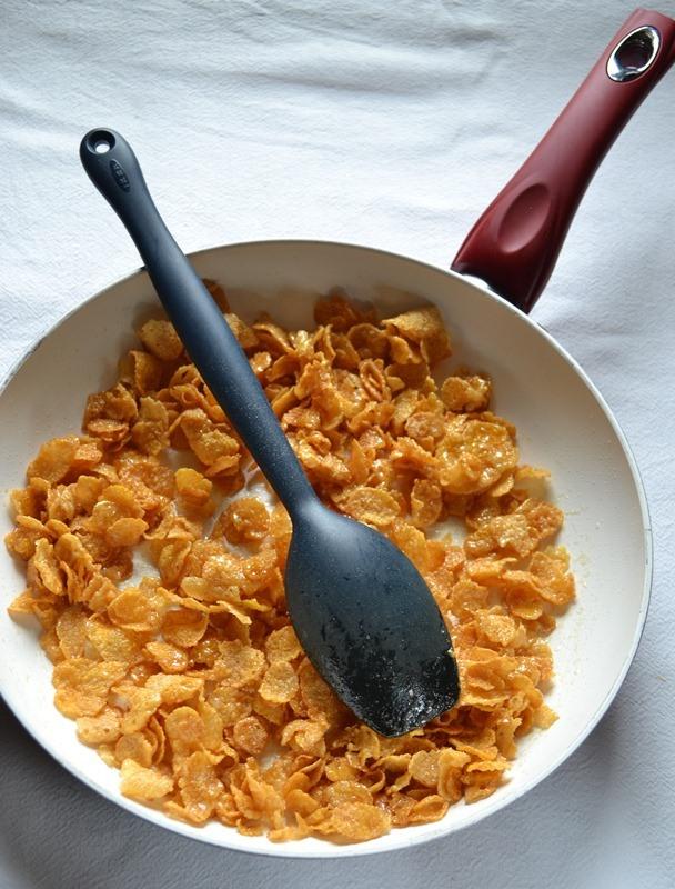 Sfornate, abbassate il forno a 180 gradi e mettete la crostata da parte. Versate il miele, lo zucchero e la Vallé+Burro in una padella capiente. Mettete sul fuoco e fate scaldare mescolando un paio di volte; quando tutto è sciolto e amalgamato e inizia a sfrigolare, unite il cornflakes e mescolate in modo da ricoprirli bene col caramello leggero che si formerà. Quando tutti i fiocchi sono ben coperti di caramello, spegnete e mettete da parte