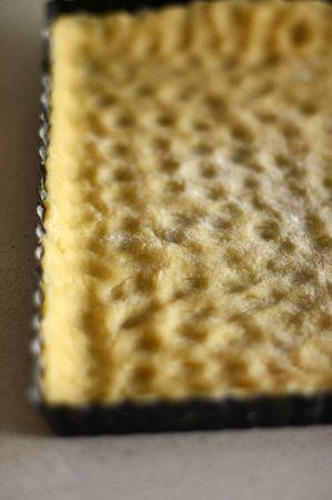 Infarinare una teglia per crostate e stendere con le mani la pasta <br />