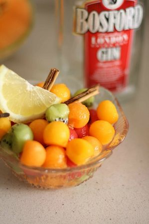 Condire la frutta con gli ingredienti della sangria (aromi, mezzo bicchierino di gin e di vino bianco)