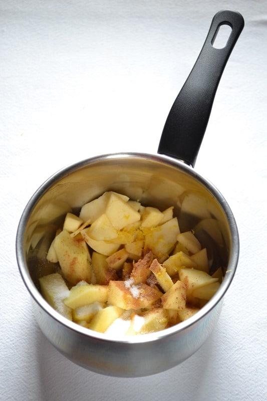 Mentre la pasta riposa in frigo, preparare la farcitura: sbucciate le mele, tagliatele a tocchetti e mettetele in un pentolino dal fondo pesante. Unite la cannella, 2 cucchiai di zucchero e la scorza di limone grattugiata e mettete a cuocere a fuoco medio. Appena l'acqua inizia a sobbollire, abbassate in fuoco, coprite e lasciate cuocere fino a quando le mele saranno morbide e un po' disfatte (circa 15 minuti), aggiungendo altra acqua se necessario. Spegnete il fuoco, schiacciate le mele con una forchetta e lasciate raffreddare (oppure lasciatele raffreddare e poi frullatele)