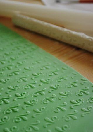 Colorare una parte di Pasta di Zucchero di verde chiaro. Passare l'apposito matterello per la decorazione oppure utilizzare un semplice centrino appoggiandolo sopra e passando il matterello