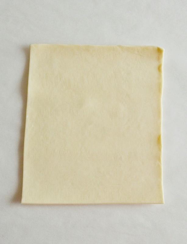 Preparate la crema sbattendo l'uovo con lo zucchero, unite l'amido e la scorza del limone. <br /> Unite il latte e fate addensare su fuoco basso sempre mescolando. <br /> Lasciate raffreddare.<br /> Da ogni rotolo di Pasta sfoglia ricavate dei rettangoli che misurino 10x12 cm circa. <br />