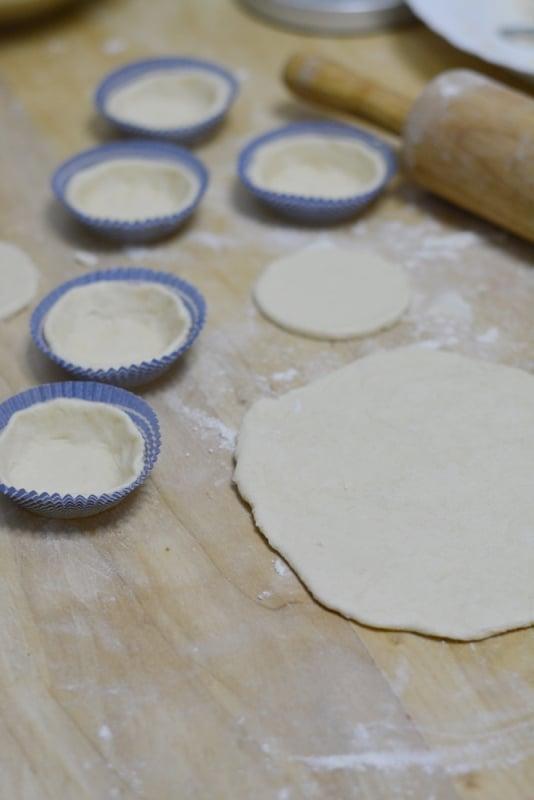 stendere la sfoglia e ricavare dei cerchi. Sistemare all'interno di pirottini di carta