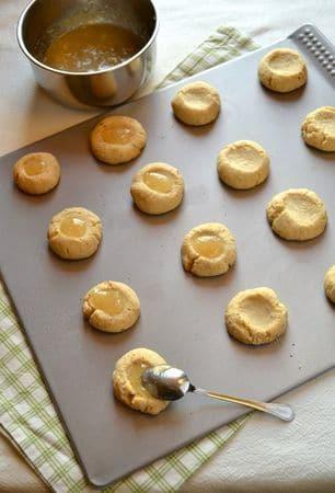 Una volta sfornati i biscotti, lasciateli riposare per 5 minuti, poi staccateli delicatamente dalla placca e metteteli a raffreddare su una gratella. Quando sono freddi, fate scaldare a fuoco dolce la marmellata di limoni in un pentolino dal fondo pesante, mescolando finché non diventa liquida. Fate cadere un cucchiaino di marmellata su ogni biscotto in modo da riempire la fossetta