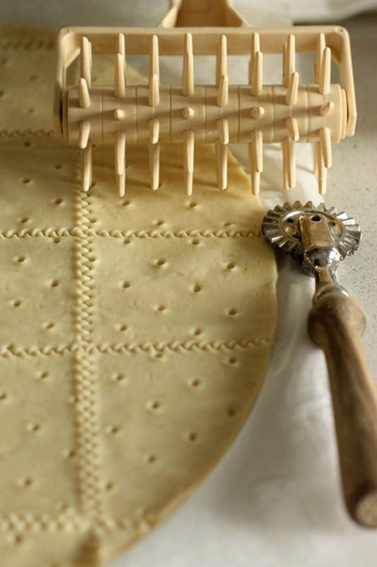 Stendere la pasta sfoglia, bucherellarla e tagliarla a quadrati con la rotella dentellata