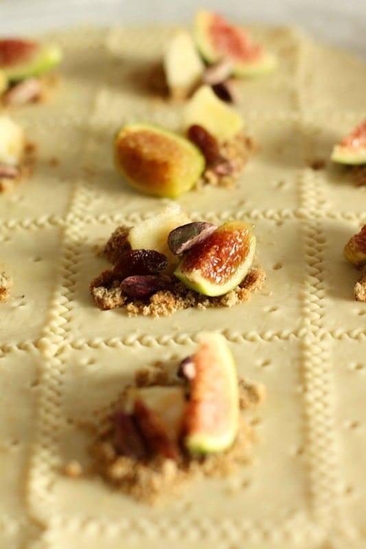 In ogni quadrato disporre un po' di biscotto sbriciolato, uno spicchio di fico, un pezzettino di mela, uno/due pistacchi, 1 acino di uva sultanina