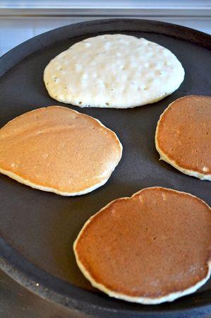 Fate scaldare una crepiera o una padella di ghisa pesante su fuoco medio. Se non avete nessuno dei due tipi di pentola, fate scaldare dell'olio vegetale neutro – per es. girasole – in una normale padella (in quantità da coprire bene il fondo). Fate cadere un cucchiaio abbondante di pastella sulla crepiera (o nell'olio) e cuocete finchè l'intera superficie è coperta da bollicine. A quel punto girate i pancakes e terminate la cottura in modo da ottenere pancakes coloriti su entrambi i lati. Mettete a riposare avvolti nella carta stagnola man mano che procedete in modo da non farli raffreddare.
