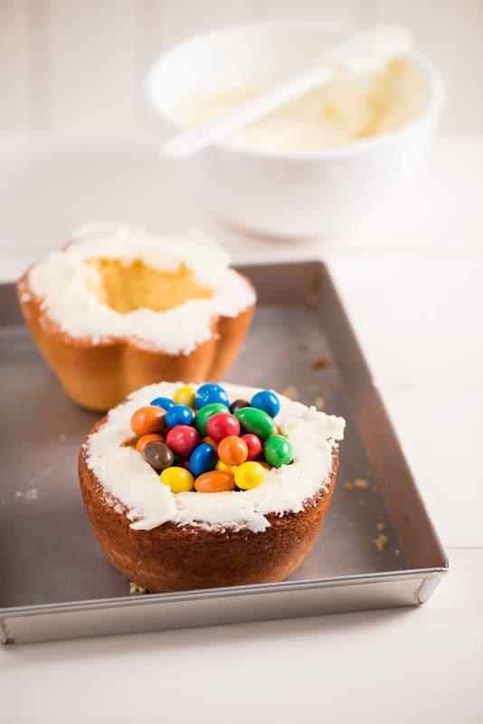 Spalmare la crema di margarina sui bordi delle due tortine, riempire la cavità con le caramelle e sovrapporle una sull'altra.