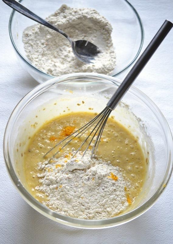 Incorporate la farina col muesli negli ingredienti liquidi a 2-3 cucchiai alla volta, mescolando bene dopo ogni aggiunta: tra un'aggiunta e l'altra, unite la scorza d'arancia grattugiata, poi spremete l'arancia e usate il succo per ammorbidire l'impasto quando diventa troppo secco; se il succo non dovesse bastare aggiungete poca acqua senza diluire troppo il composto, deve rimanere morbido ma non liquido
