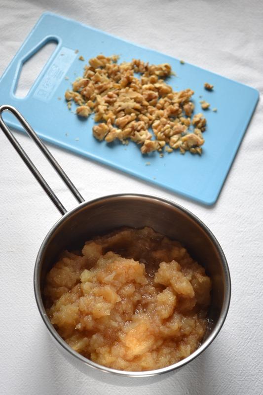 Sbucciate le mele e tagliatele a pezzetti; versate tutto in un pentolino dal fondo pesante. Aggiungete 2 cucchiai d'acqua e fate cuocere coperto per 10- 15 minuti circa (fino a quando non si disfano) a fuoco medio, controllando che non attacchino (in tal caso aggiungete poca acqua). Schiacciate le mele con una forchetta fino a ridurle in puré e lasciate raffreddare. Nel frattempo, tritate grossolanamente le noci.