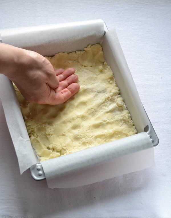 Versate le briciole in un stampo quadrato (20x20) rivestito con due fogli di carta forno incrociati. Pressate le briciole con la mano in modo da uniformare il fondo e mettete mezz'ora in frigo.
