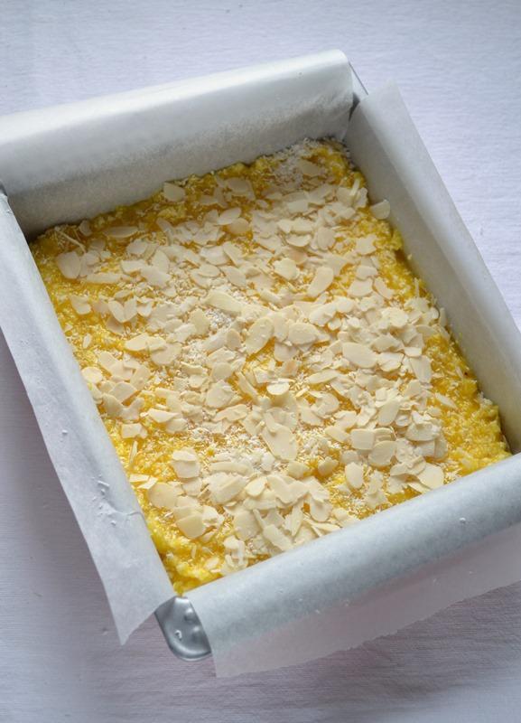 4.Versate la crema sulla base e coprite col cocco rimasto, le scaglie di mandorle e infornate per 35 minuti circa (25 sul piano mediano, 10 su quello inferiore).