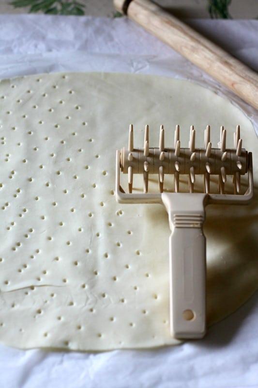 Srotolare la sfoglia Vallé e bucherellarla. Con una formina ricavare dei cerchi.